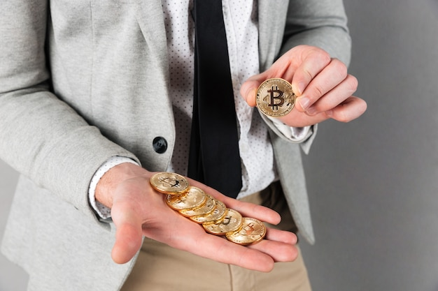 Close up of man holding stack of golden bitcoins