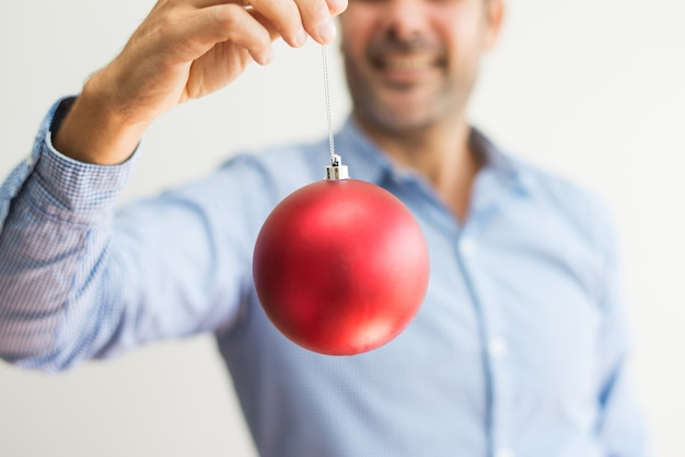Close-up of man holding string of christmas ball and viewing it