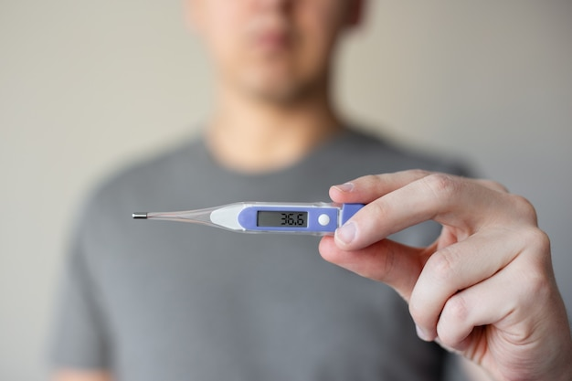 Close up of man holding thermometer in his hands, temperature is 36.6 degrees celsius