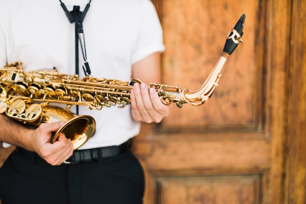 Close up of man holding tightly sax