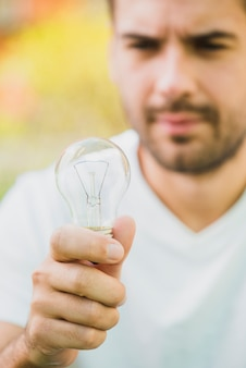 Close-up of man holding transparent light bulb