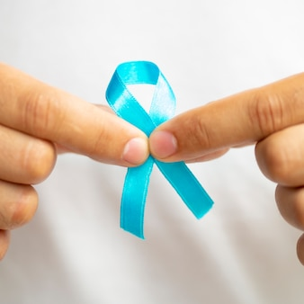 Close-up man holding up blue ribbon