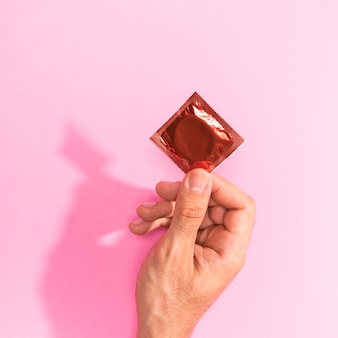 Close-up man holding up a red condom