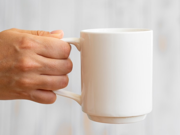 Close-up man holding up white mug