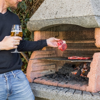 Close-up of man holding wineglass grilling beef in barbecue