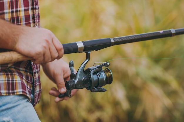 Primo piano un uomo tiene e srotola un mulinello da pesca tra le mani su uno sfondo marrone sfocato. stile di vita, ricreazione, concetto di svago del pescatore. copia spazio per la pubblicità. con posto per il testo.