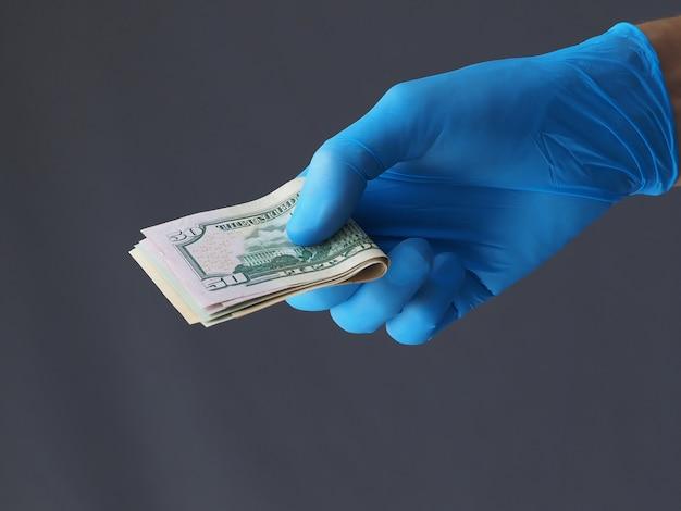 Крупный план. мужчина в синих перчатках держит доллары сша. серый фон