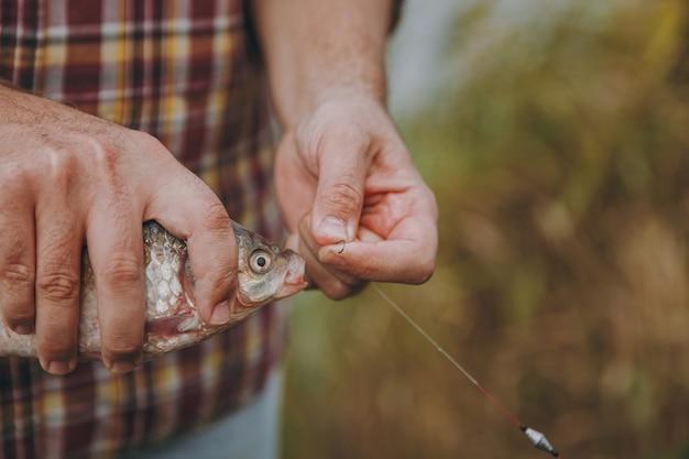 체크무늬 셔츠를 입은 남자는 흐릿한 파스텔 갈색 배경의 낚싯대에 있는 갈고리에서 잡은 물고기를 제거합니다. 라이프 스타일, 레크리에이션, 어부의 레저 개념. 광고 공간을 복사합니다.