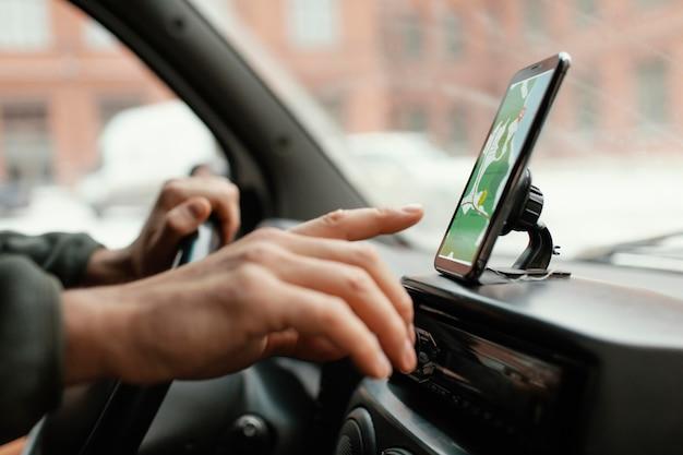 Крупным планом человек в машине с картой на мобильном телефоне