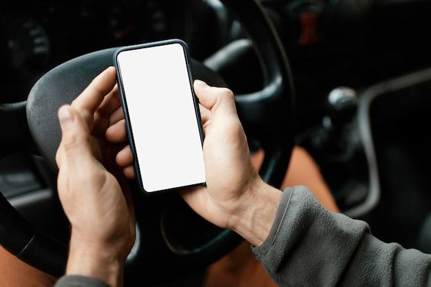 携帯電話で車の中で男をクローズアップ