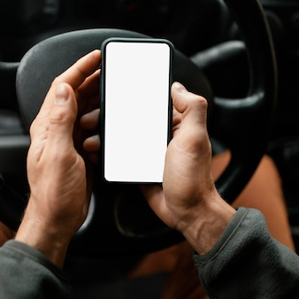 Крупным планом человек в машине с мобильным телефоном