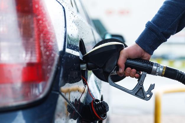 クローズアップ-男はガソリンスタンドで彼の車のタンクを満たしています