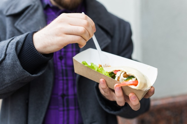 Close-up of man is holding falafel sandwich in paper bag. healthy street food concept, oriental cuisine.
