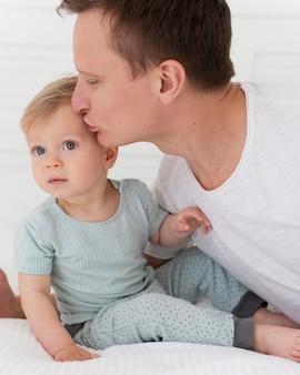 Крупным планом мужчина целует малыша