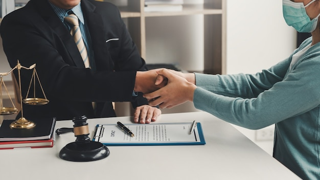 Close up of man lawyer hand and woman client shaking hand collaborate on working agreements with contract documents at the office.