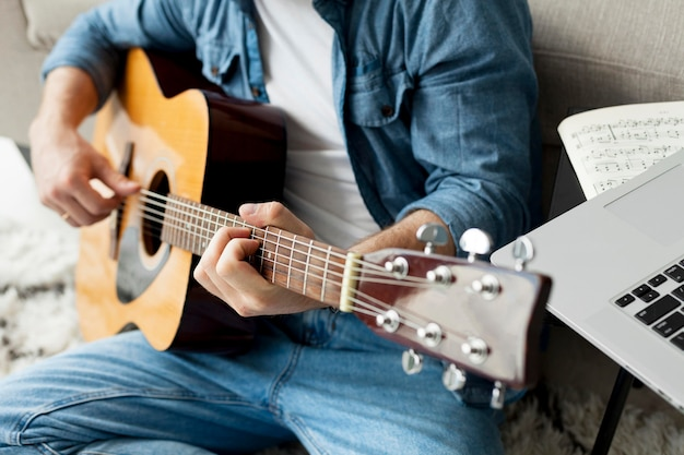 クローズアップ男がギターを弾く方法を学ぶ