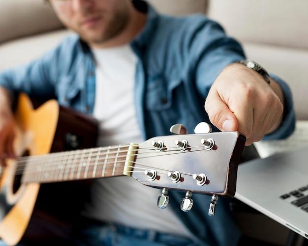 기타를 튜닝하는 방법을 배우는 근접 남자