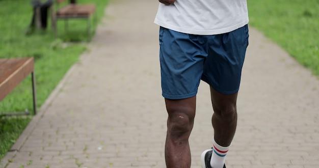 남자 다리를 닫습니다 운동 선수 주자 실행 도시에 있는 공원에서 훈련입니다. 아침 운동. 건강한 라이프 스타일의 개념입니다.