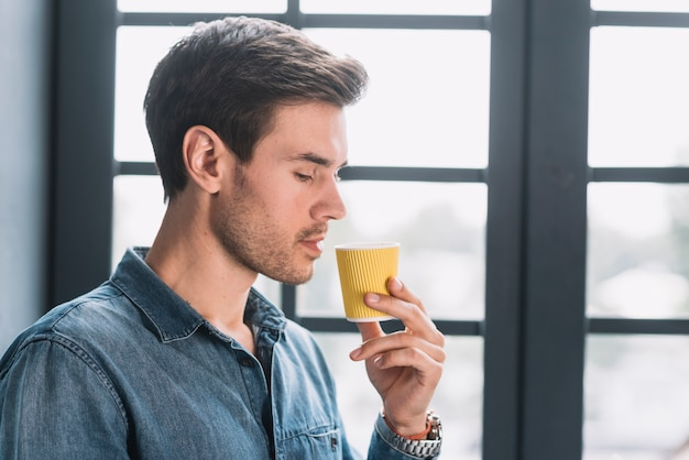 Close-up of a man looking at take away coffee cup in hand