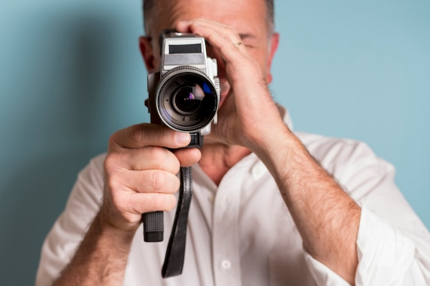 Close-up of a man looking through 8mm film camera against blue backdrop