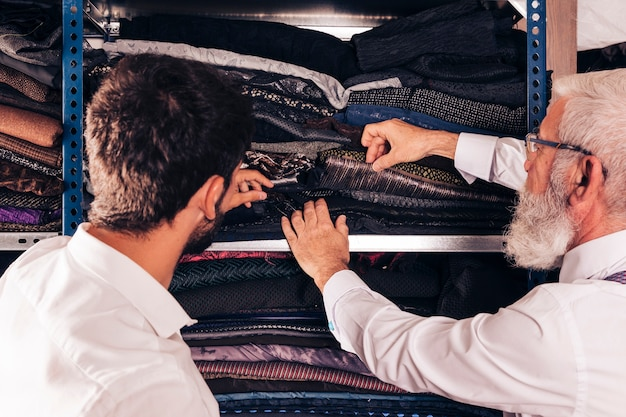 Close-up of man and male senior tailor selecting the fabric in the shelf