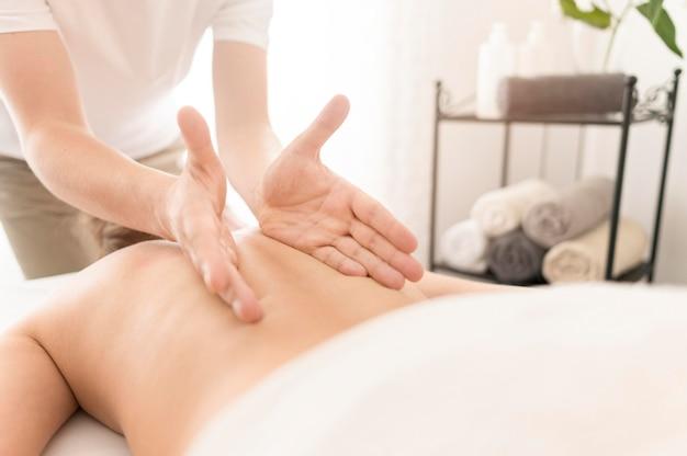 Uomo massaggiante del primo piano client