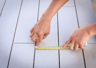 Close up Man measuring timber floor with measuring tape.