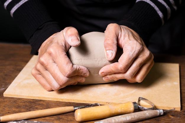 Close-up uomo mescolando argilla