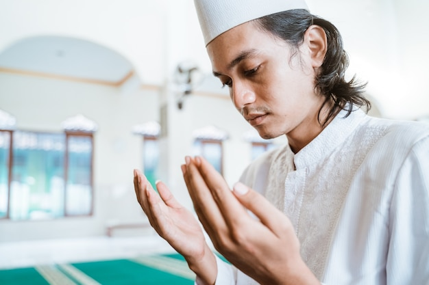 Крупным планом мужчина-мусульманин, совершающий молитву в мечети