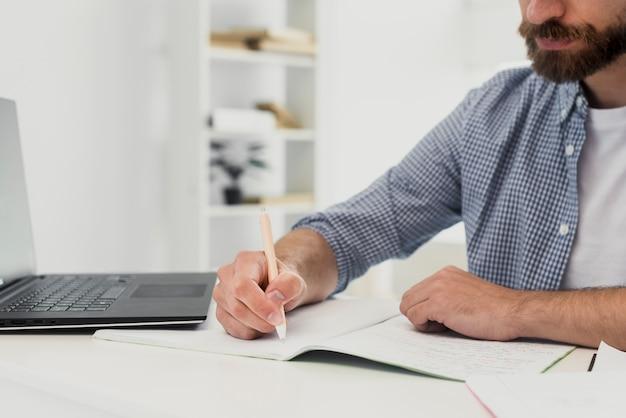 Close-up man at office writing mock-up