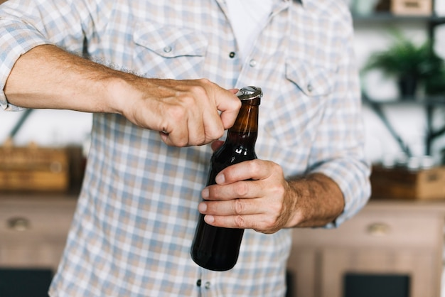 Close-up of a man opening the beer bottle with opener