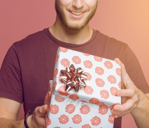 Close-up of man opening floral gift box against colored background