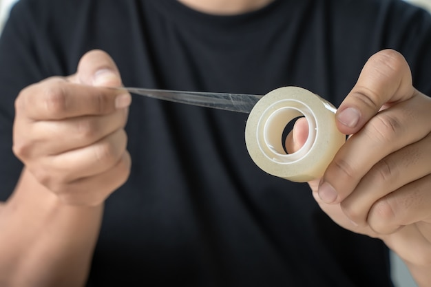 Close up of a man packaging tape roll adhesive tap