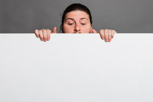 Close-up of a man peeking behind the white card paper against grey background