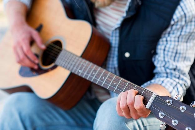Крупным планом человек играет на акустической гитаре