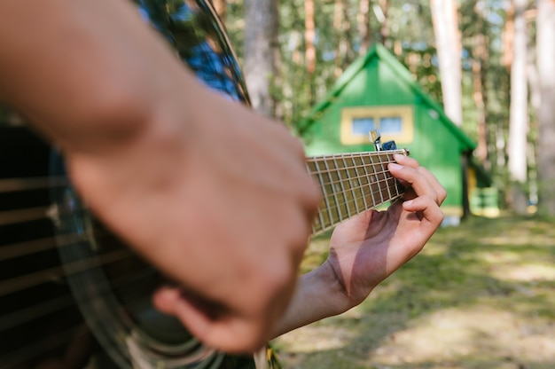 Close-up of a man playing the guitar. against the background of a forest house in nature.