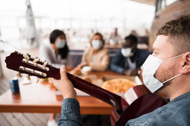 テーブルでギターを弾くクローズアップの男