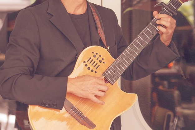 Close-up of a man playing the guitar.