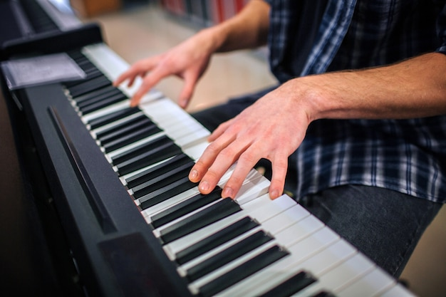 Close up of man playing on keyboard. he sits alone in room.