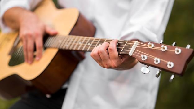 自然の中でギターを弾くクローズアップ男