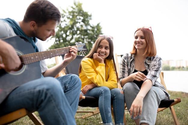屋外でギターを弾く男をクローズアップ