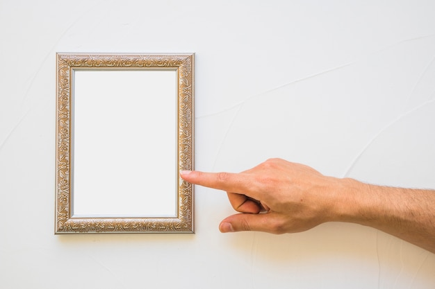 Close-up of man pointing at white golden picture frame on wall