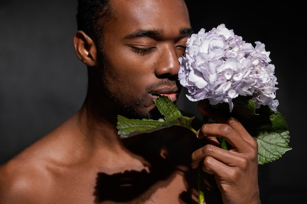 美しい花でポーズをとるクローズアップ男