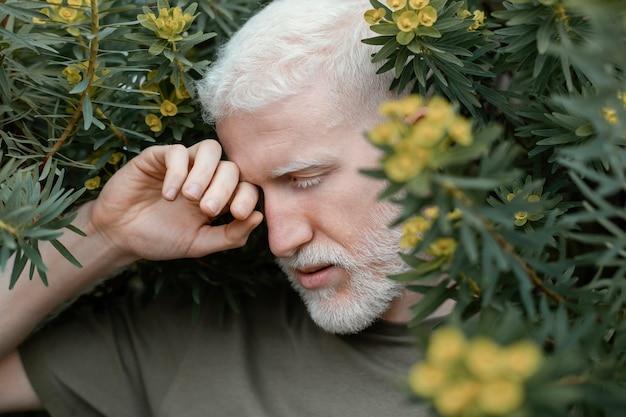 植物でポーズをとる男のクローズアップ