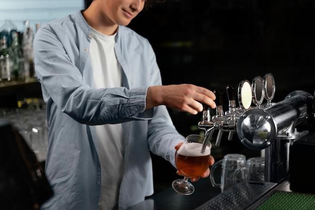 Uomo del primo piano che versa birra in vetro