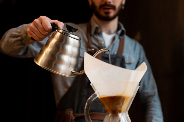Close-up of man pouring coffee from pot in filter