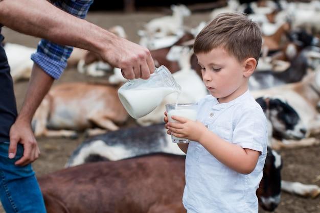 小さな男の子に牛乳を注ぐクローズアップ男
