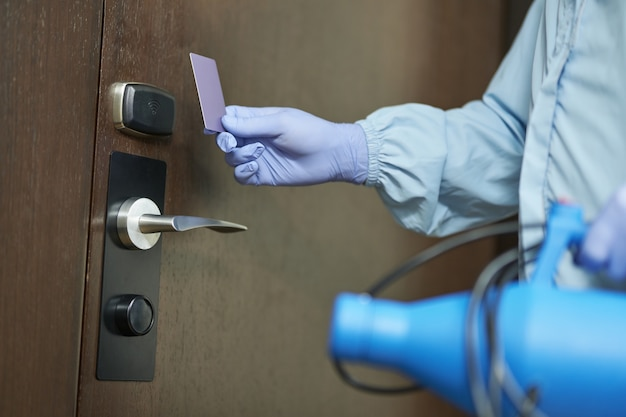 Close up of man protective gloves when going to enter the room and disinfect. coronavirus and quarantine concept