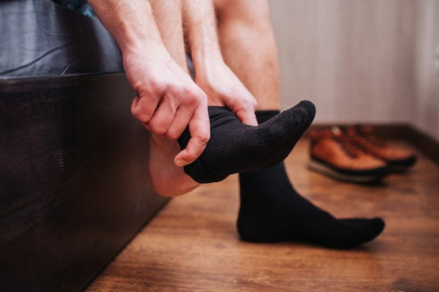 Close-up. a man puts a sock. he is sitting on his bed