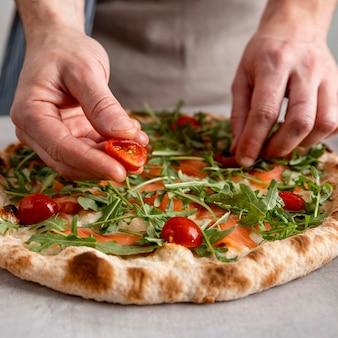 Мужчина крупным планом кладет помидоры на тесто для запеченной пиццы с ломтиками копченого лосося